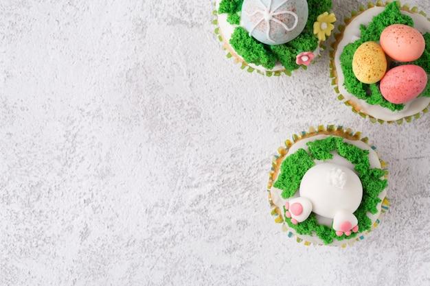 Petits gâteaux de fête avec lapin drôle, des œufs et de l'herbe sur fond blanc. concept de vacances de pâques. vue de dessus avec espace de copie Photo Premium