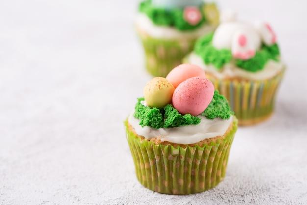Petits gâteaux de fête avec des œufs de mastic et de l'herbe sur fond clair. concept de vacances de pâques. espace de copie Photo Premium