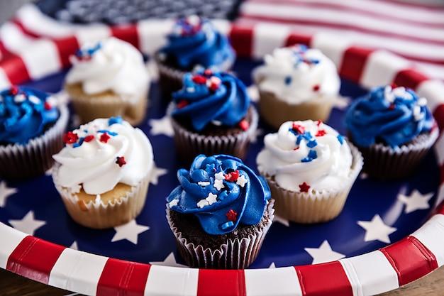 Petits gâteaux de juillet sur une assiette en carton avec un drapeau américain Photo Premium