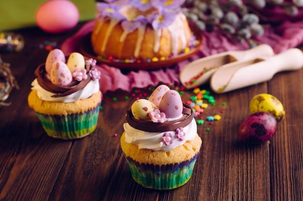 Petits gâteaux de pâques décorés avec des œufs en bonbon au nid Photo Premium