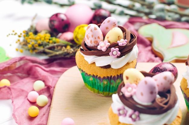 Petits gâteaux de pâques décorés avec des œufs de bonbons au nid sur la table du dîner de pâques Photo Premium