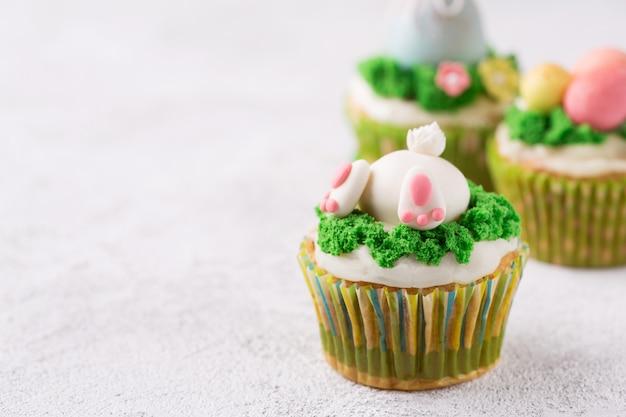 Petits gâteaux de pâques avec lapin drôle et herbe sur fond blanc. concept de vacances de pâques Photo Premium