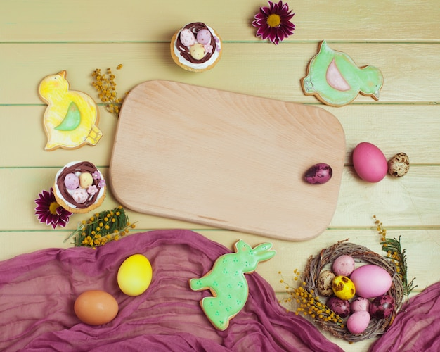 Petits gâteaux de pâques, pains d'épices, oeufs peints autour d'un plateau vide Photo Premium