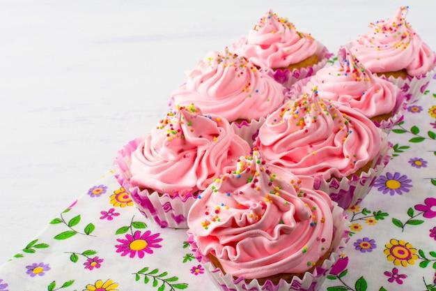 Petits gâteaux roses sur une serviette florale Photo Premium
