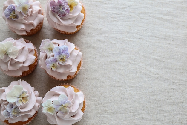 Petits gâteaux violets avec espace de copie de fleurs comestibles sucrées Photo Premium