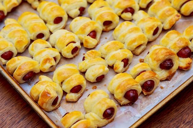 Petits hot dogs roulés dans la pâte et cuits au four Photo Premium