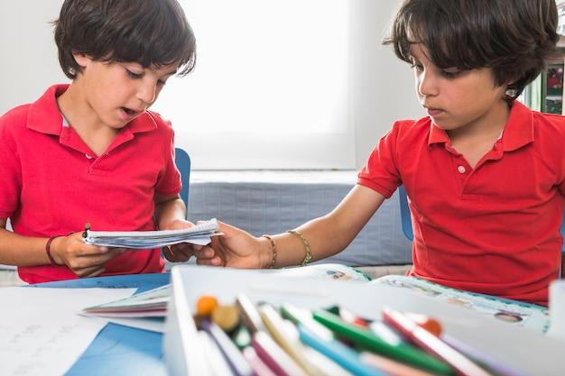 Petits jumeaux faisant des métiers en papier ensemble Photo gratuit