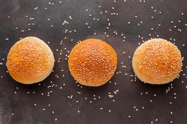 Petits pains aux graines de sésame et fond texturé Photo gratuit
