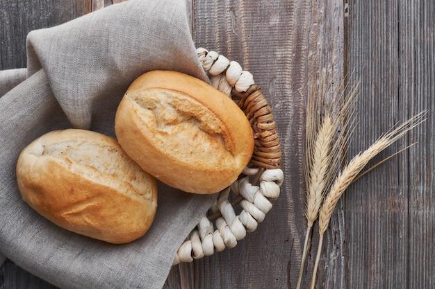 Petits pains dans un panier sur du bois rustique avec des épis de blé Photo Premium