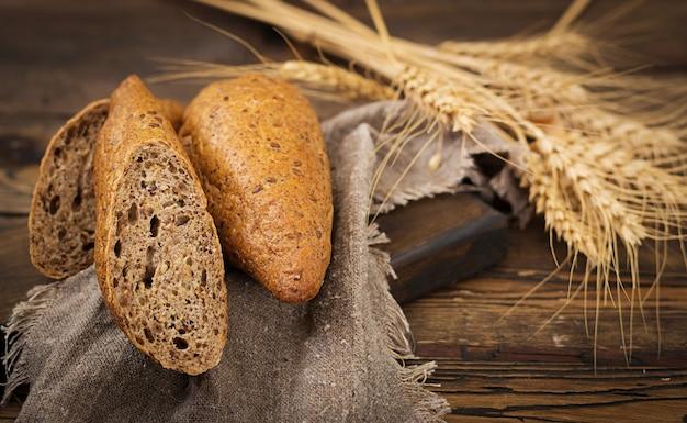 Petits pains de farine de grains entiers avec l'ajout de graines de lin sur un fond en bois. Photo Premium