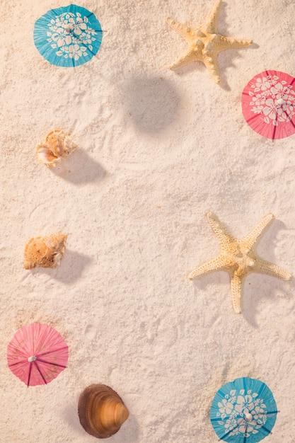 Petits parapluies avec des coquillages sur la plage Photo gratuit