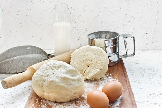 Pétrir la pâte. cuisson de la pâte. pâte sur une planche en bois avec un rouleau à pâtisserie. Photo Premium