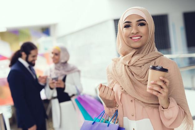 Peuple arabe debout avec un café dans le centre commercial après le shopping Photo Premium
