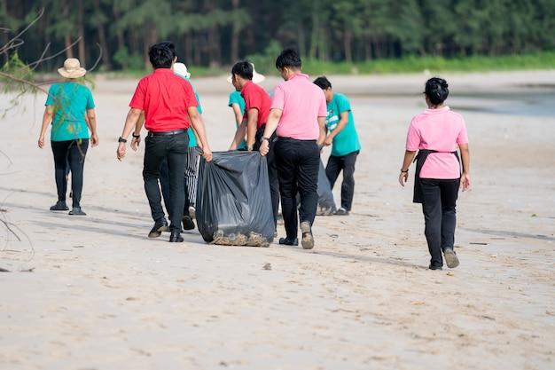 Un peuple asiatique nettoie une plage de sable blanc Photo Premium
