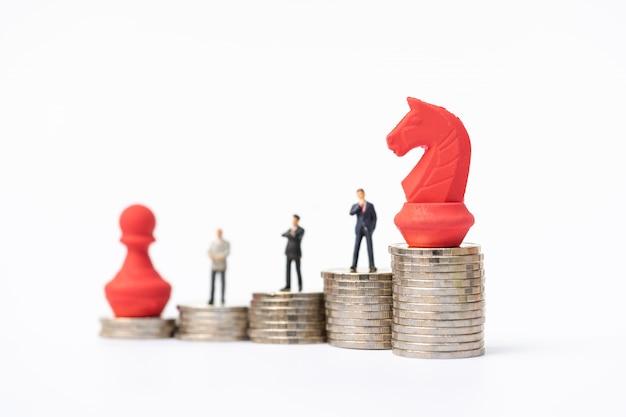 Peuple miniature, hommes d'affaires debout sur une pile de pièces avec une pièce d'échecs rouge. Photo Premium