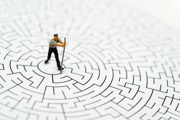 Peuple Miniature, Ouvrier Abattant Les Murs Dans Le Labyrinthe Photo Premium