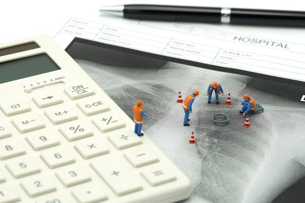 Peuple miniature ouvrier sur calculatrice blanche avec rayon x du poumon Photo Premium