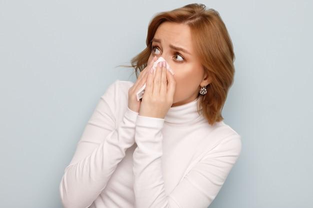 Peur Jeune Femme En Col Roulé Blanc Avec Le Nez Mouchoir Serviette, à La Recherche De La Source D'allergie. Photo Premium
