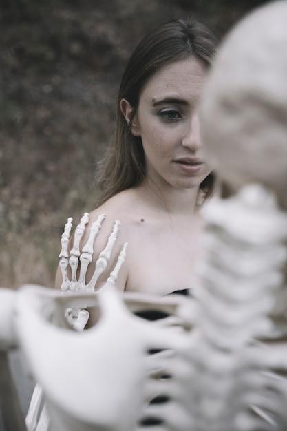 Peur Jeune Femme Derrière Le Squelette Photo gratuit