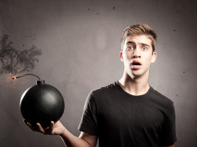 Peur Jeune Homme Tenant Une Bombe à L'ancienne Photo Premium