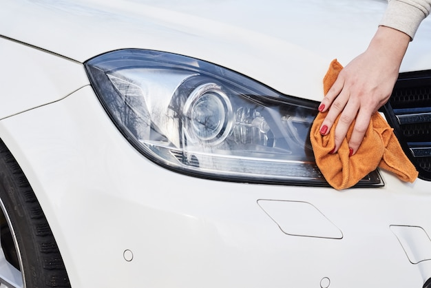 Phare de voiture femme propre avec un chiffon en microfibre Photo Premium