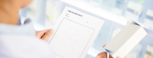 Pharmacien détenant une ordonnance vérifiant un médicament en pharmacie Photo Premium