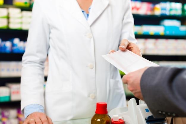 Pharmacien femme avec un client en pharmacie Photo Premium