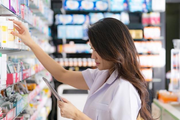 Pharmacien femme prenant un médicament sur l'étagère et utilise une tablette numérique à la pharmacie Photo Premium