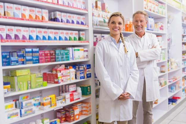 Pharmacien avec son stagiaire debout et souriant à la caméra Photo Premium