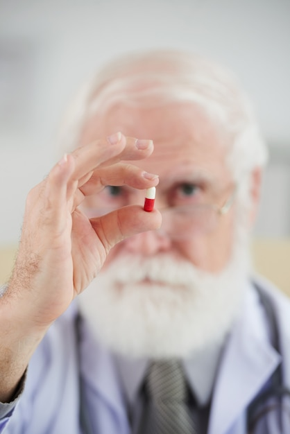 Pharmacien tenant une capsule Photo gratuit