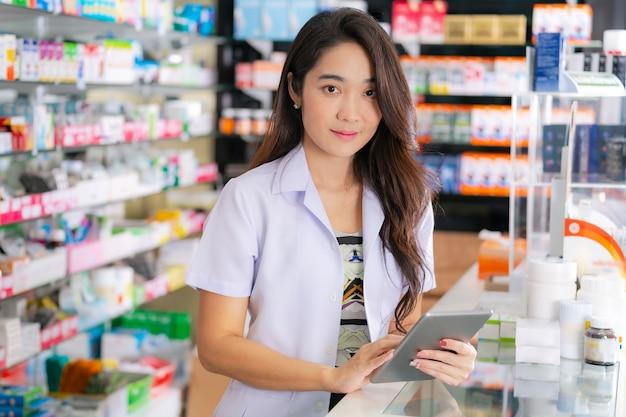 Une pharmacienne asiatique utilise une tablette numérique à la pharmacie Photo Premium