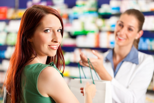 Pharmacienne dans sa pharmacie avec un client Photo Premium