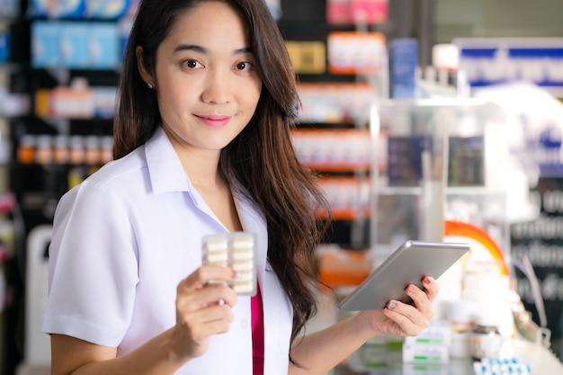 Une pharmacienne tient une boîte de médicaments et utilise une tablette numérique en pharmacie Photo Premium