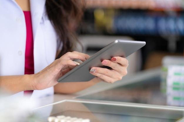 Une pharmacienne utilise une tablette numérique à la pharmacie Photo Premium