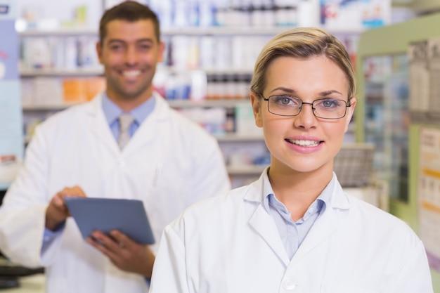 Pharmaciens regardant la caméra à la pharmacie de l'hôpital Photo Premium