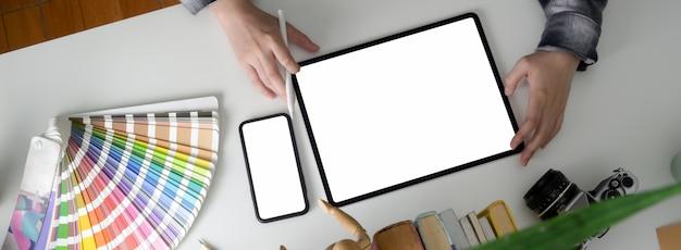 Photo Aérienne D'un Designer Féminin Travaillant Avec Une Tablette à écran Vide Et Un Smartphone Photo Premium