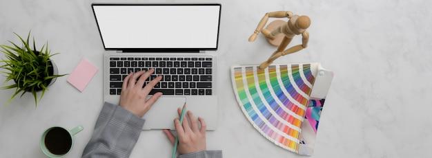 Photo Aérienne D'un Designer Travaillant Sur Une Maquette D'ordinateur Portable Et De Fournitures De Designer Sur Une Table En Marbre Photo Premium
