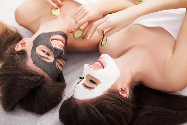 Une photo d'amis de deux filles se détendre avec des masques sur fond blanc Photo Premium