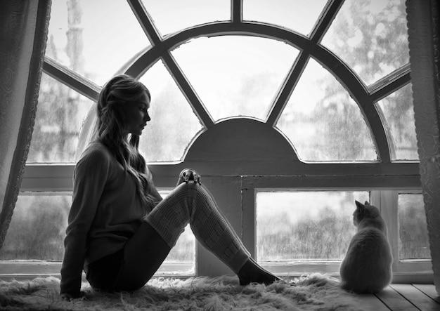 Photo d'art fille blonde et fenêtre de chat blanc assis Photo Premium