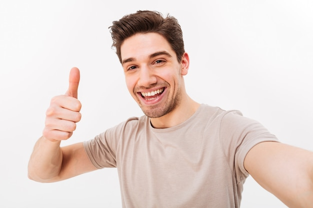 Photo De Bel Homme En T-shirt Décontracté Et Poils Sur Le Visage Souriant à La Caméra Avec Le Pouce Vers Le Haut Tout En Prenant Selfie, Isolé Sur Mur Blanc Photo Premium