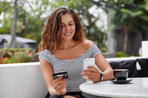 Photo De Belle Femme Touriste Utilise Un Téléphone Moderne Et Une Carte De Crédit Pour Réserver Un Billet En Ligne Photo gratuit