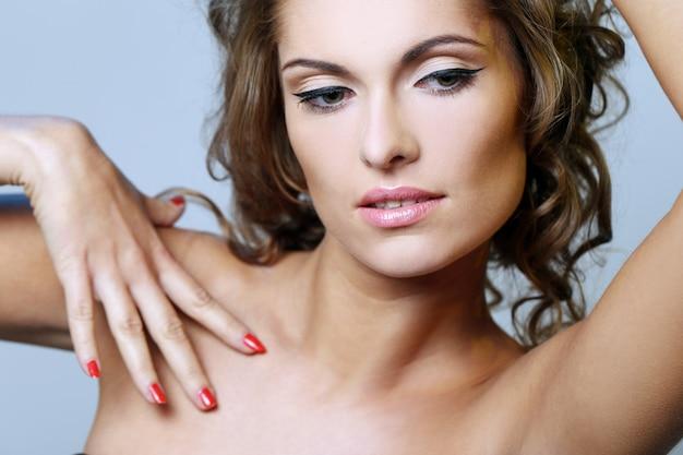 Photo de belle fille et elle touche sa peau, regarde en bas Photo gratuit