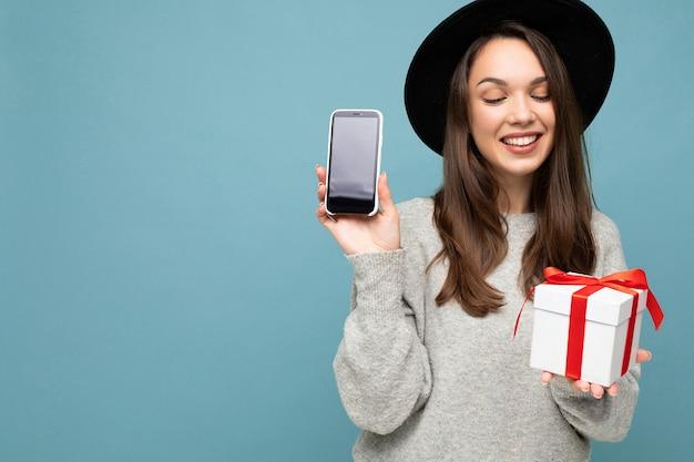 Photo De Belle Heureuse Jeune Femme Brune Joyeuse Isolée Sur Fond Bleu Portant Le Mur Photo Premium
