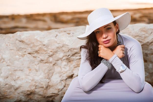 Photo d'une belle jeune femme élégante avec un chapeau au bord de la mer Photo Premium