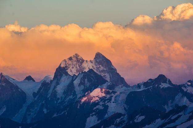 Photo de belles montagnes au coucher du soleil dans les nuages Photo Premium