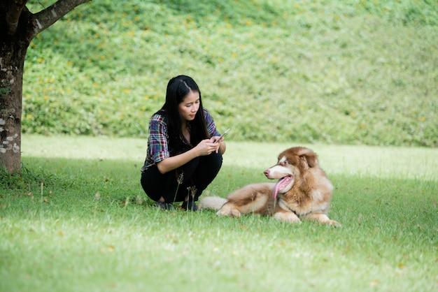 Photo de capture de belle jeune femme avec son petit chien dans un parc en plein air. portrait de mode de vie. Photo gratuit