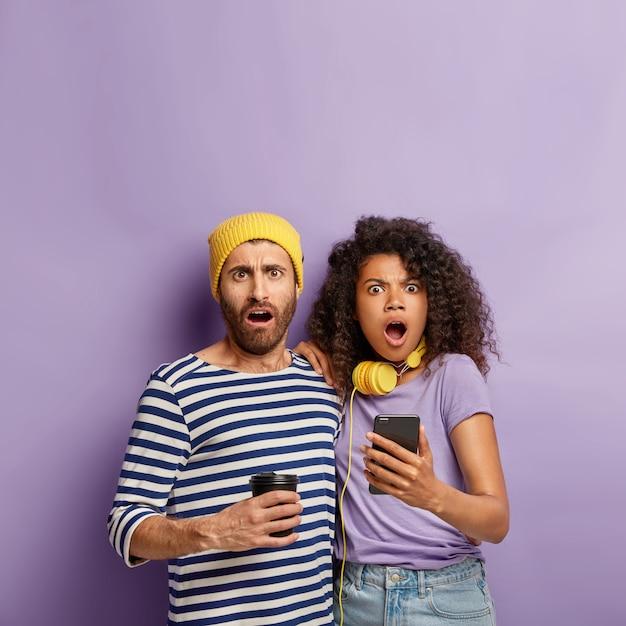 Photo D'un Couple Métis étonné Avec Des Expressions Omg, Recevoir Des Nouvelles Horribles, Une Femme Afro Tient Un Smartphone, Lit L'article En Ligne Photo gratuit