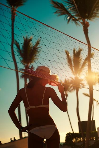 Photo Dans Un Style Rétro De Fille Modèle Sexy En Bikini Blanc Avec Filet De Volley-ball Sur La Plage Et Les Palmiers Derrière Le Ciel D'été Bleu Photo gratuit