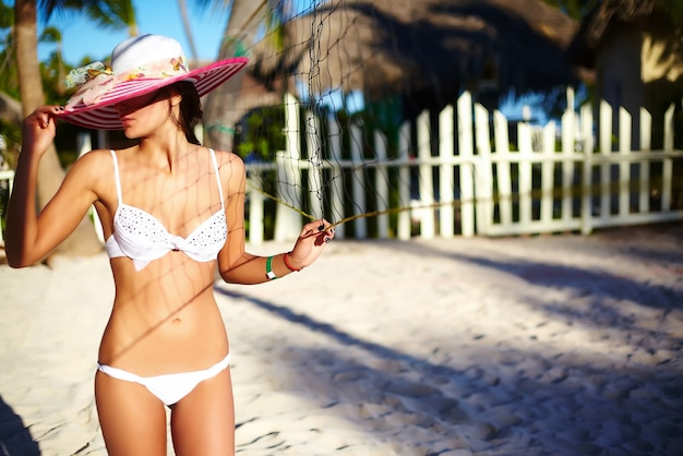 Photo Dans Le Style Rétro De La Fille Modèle Sexy En Bikini Blanc Avec Filet De Volley-ball Sur La Plage Et Les Paumes Derrière Le Magnifique Coucher De Soleil Photo gratuit