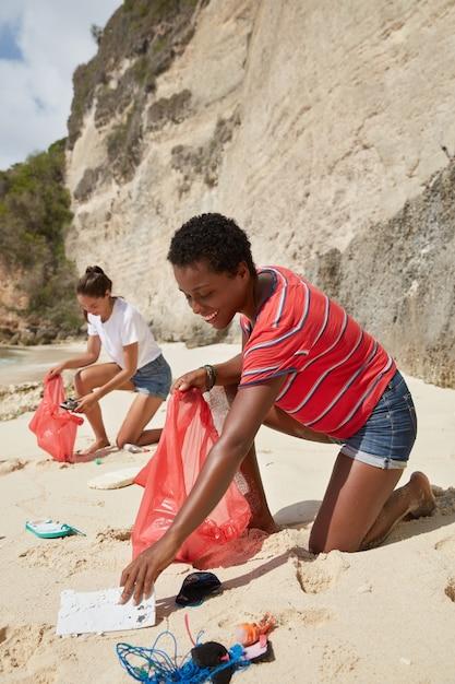 Photo De Deux Femmes Actives Métisses Ramasser Des Déchets Sur Une Plage De Sable Photo gratuit